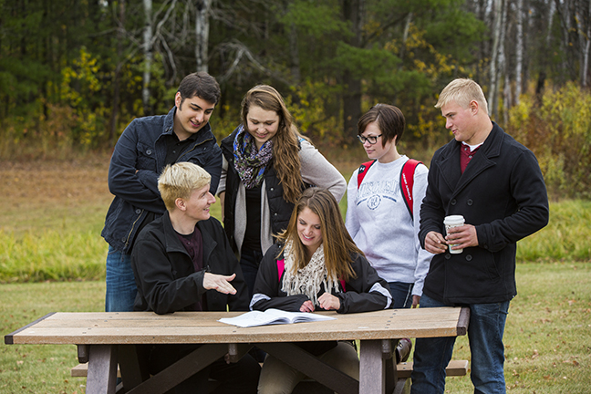 A group of students outside sitting and talking at a picnic table