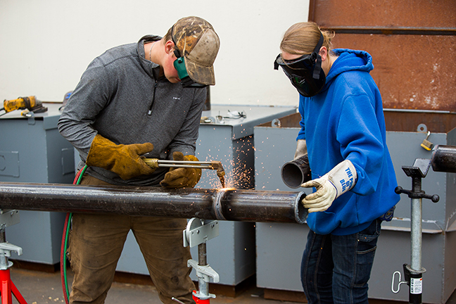Students welding a pipe