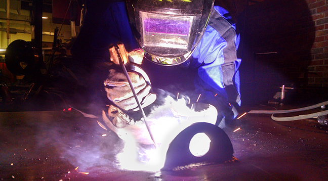 A student welding and sparks flying