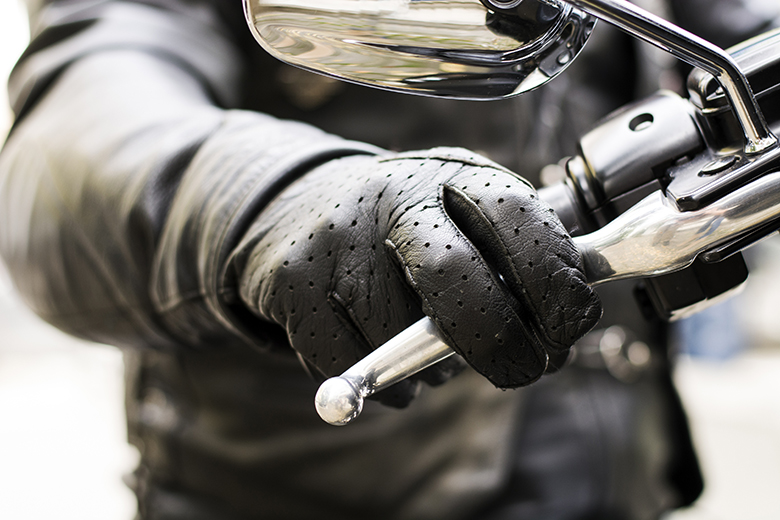 Close up of a black leather glove gripping motorcycle handlebar