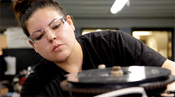 A marine repair student wearing goggles and analyzing a part