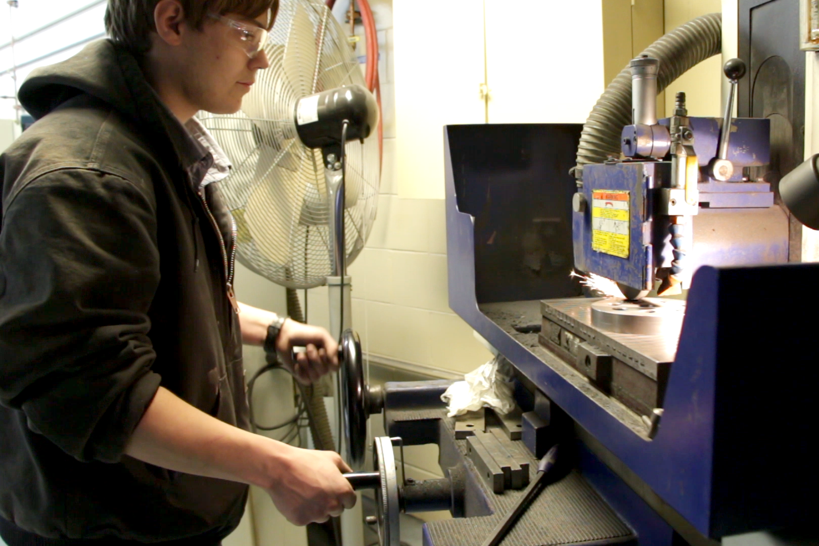 A student operating a machine