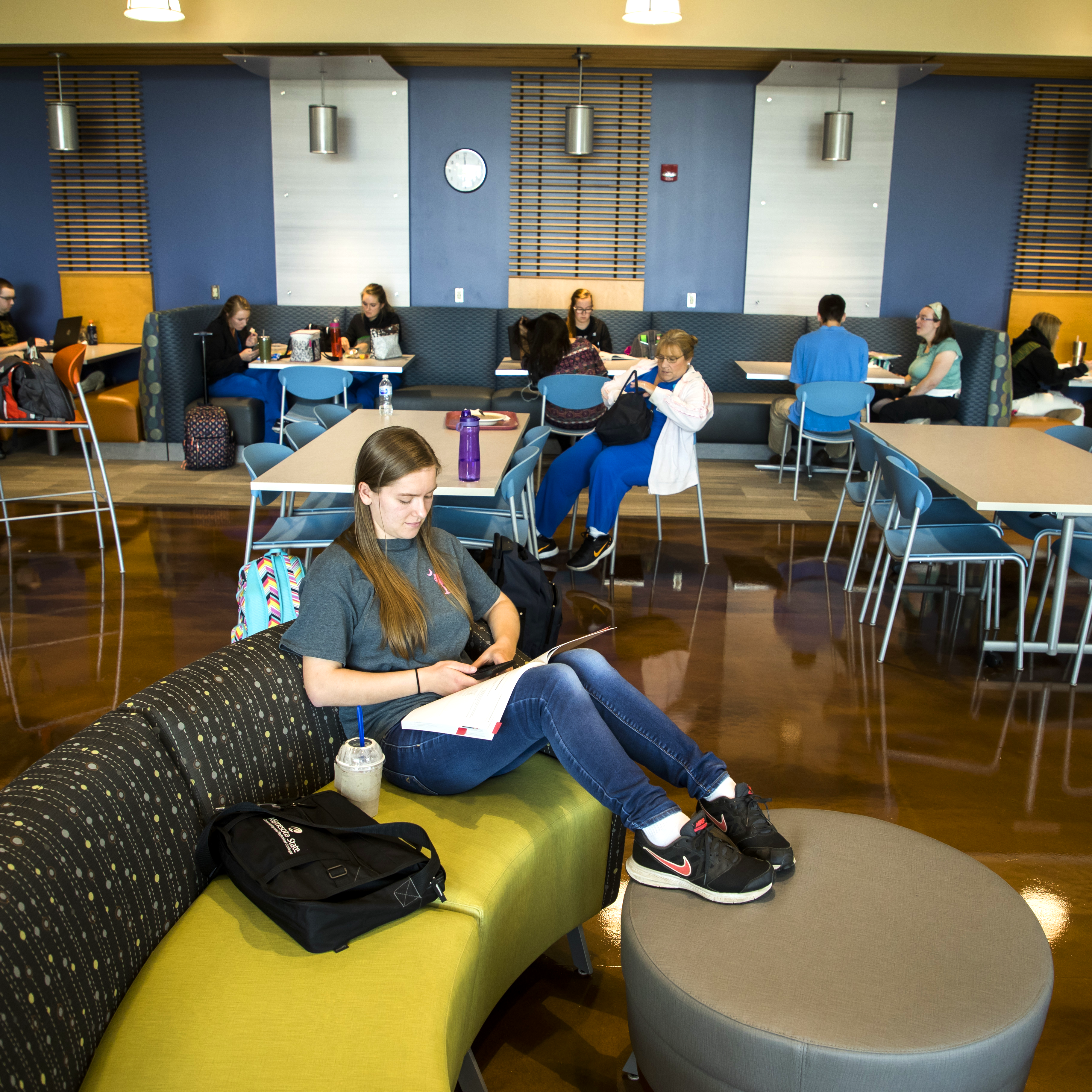 Image of a student relaxing and studying in the WITC-New Richmond commons area