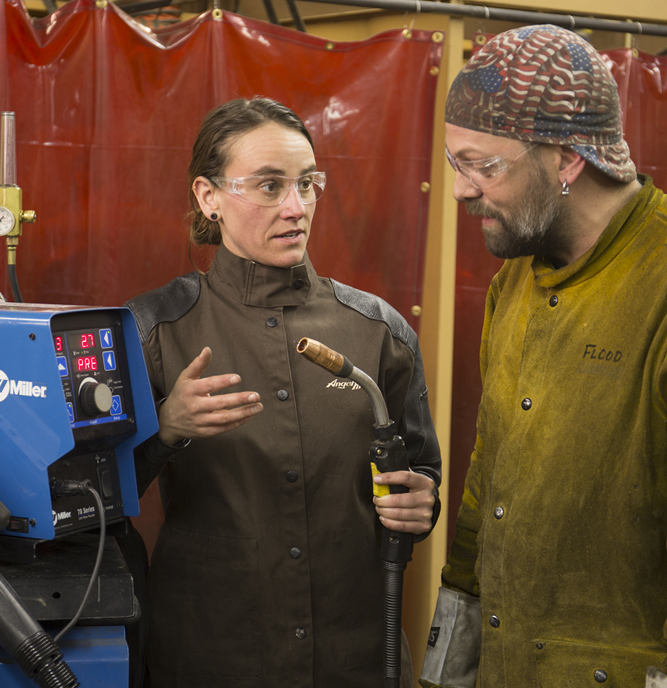 Female welding instructor works with a male student