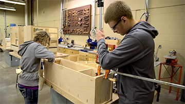 Students working on a cabinet they made