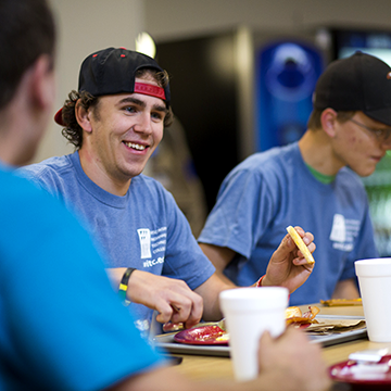 Student sitting in a group, eating and laughing.