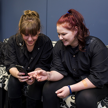 Two cosmetology students looking at a phone and laughing