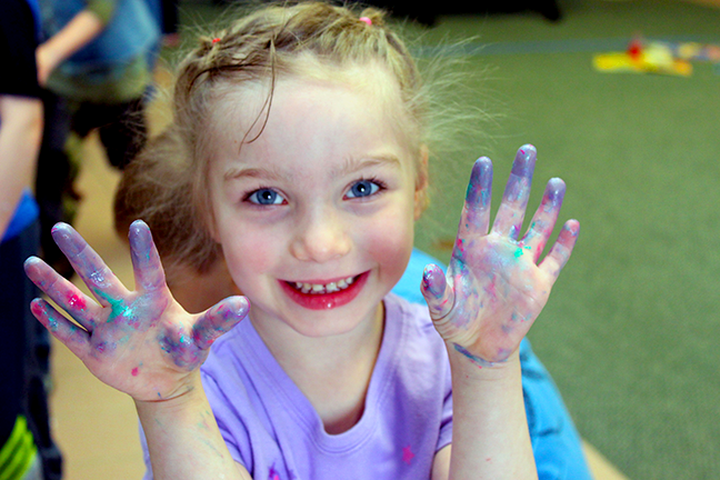 Child smiling and holding up messy and sparkly hands