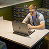Young man sits at a booth in Ashland with headphones in and working at a laptop.