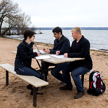 Group of WITC students sitting by Lake Superior at a picnic table