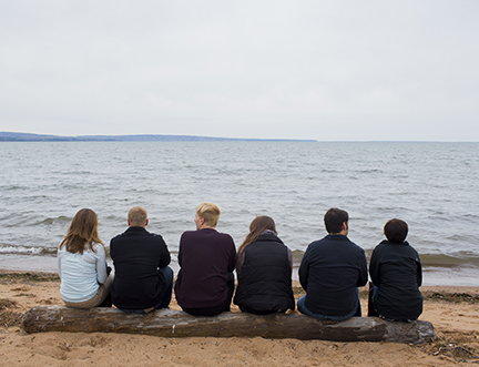 Students sitting on a log at the beach looking out toward Lake Superior