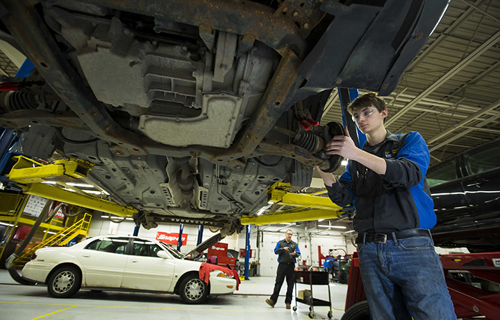 Automotive student repairing the brakes of a car in the automotive lab on campus