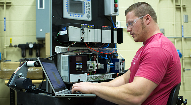 A student working on a computer in the industrial systems lab