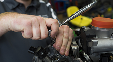 Close up of hands repairing an engine