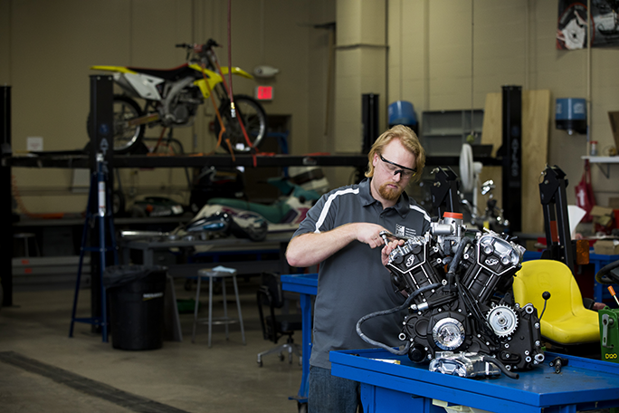 A student working on a motorcycle in the power sports lab on campus