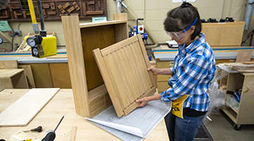 A student working on the production of a cabinet
