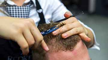 Close up of cosmetology student cutting hair