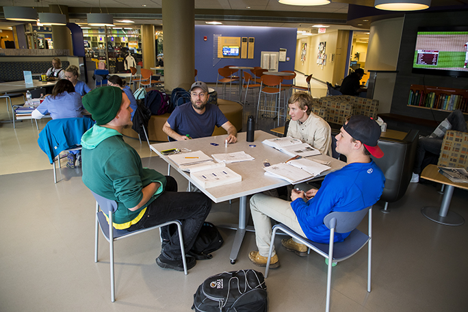 A group of students sitting at a table and studying with their books